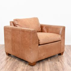 This cube chair is upholstered in a durable distressed leather fabric in a tan caramel hue. This armchair has minor cosmetic wear but is otherwise in great condition with comfortable stuffed cushions and tapered wood block feet. Contemporary chair perfect for a man cave! #contemporary #chairs #armchair #sandiegovintage #vintagefurniture