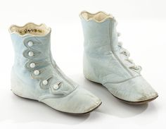 Circa 1870s Child's High Top Shoes. The scalloped upper vamp adds a special touch to the look of these light blue kid leather shoes. Six pearl colored buttons are used to fasten the high top shoes.  Via Glenbow Museum.