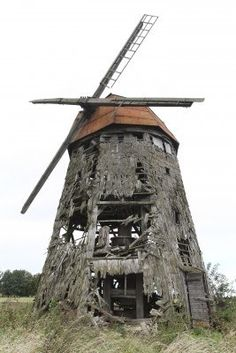 Front view of an old scary abandoned wooden windmill. I feel like this would be excellent to build an outdoor haunted trail around.