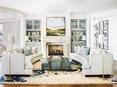 Beautiful pale blue green and neutral light living room curved couches sofas marsh painting above fireplace, built ins with cabinets gallery wall