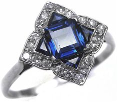 Art Deco sapphire and diamond ring, circa 1915.  It has a lozenge cluster of sapphires at the center, formed by a square cut and four triangular cut sapphires, with a border of single cut diamonds, a pierced gallery, and a plain shank. Via Diamonds in the Library.