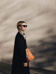 Black cashmere coat, Acne Studios sunglasses & knit jumper, Mansur Gavriel bag. Via Mija