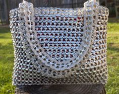 145+ pop tabs were used to make this upcycled eco-friendly handbag.  Tabs were thoroughly inspected & cleaned for quality purposes. Nylon thread was used because of its light and durable properties.  Interior of bag has hello kitty design.  Handbag Dimensions: Approximate Height 8.5 | Width: 7 | Depth: 7.5  Handles Dimensions: Approximate Height 22.5 | Width 7  If you have any questions or would like to order this handbag in a different color feel free to email me.