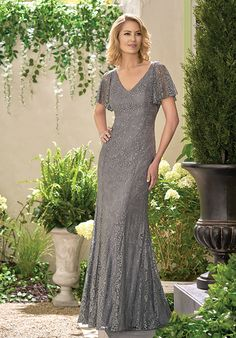 Lace with Stretch lining dress with a v-neckline, loose sleeves that hang from the shoulder, and beaded bodice and sleeves - all in the color silver.