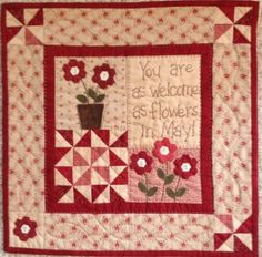 """This little welcoming quilt is just 14"""" square.  It features a bit of appliqué, a bit of embroidery, and those cute little English paper pieced hexagon flowers made from 1/4"""" hexies.The pattern includes a pack of the paper pieces.The kit includes all the fabrics for the top, back, and binding as well as the pattern with the paper pieces."""