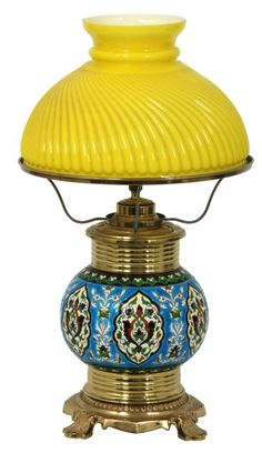 Longwy Pottery Oil Lamp. Brass lamp base has a bulbous Longwy pottery insert with colorful filigree borders and panels; brass oil canister with 10 in. dia. shade support ring. The 6.25 in. high x 10 in. dia. cased yellow glass shade has a relief gadrooned pattern.