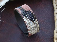 This American Indian beaded bracelet with the mirrored eagle feather is a new pattern to add to any Southwest collection. The bracelet is a leather band with a heavy duty snap. The Leather Band is vegetable tanned, condition and stained with your choice of leather stain. Antique Black Antique Dark Brown Antique Mahogany Antique Tan Glass Delica 15/0 seed beads are then woven with patience and carefully placed onto the leather band in this new pattern .The eagle feathers pop out of this Southwest