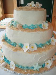 Beach Wedding Cake - 3 tiered beach themed wedding cake. graham cracker sand, gum paste plumeria, fondant and chocolate seashells