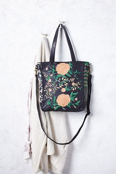 El Cosmica Tote   Buttery soft leather tote bag featuring beautiful floral embroidery and bead accents.  Zip top closure with zip and slip pockets on the inside and a hidden zip pocket in back.