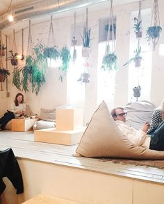 "traveling in amsterdam | the next day we decided to explore the ""pijp"" area. we went to coffee & cocounts first. it's a former theater transformed into a giant coffee shop and cafe. it was definitely busy (we went on the weekend though) but it was so gorgeous! loved the scandinavian vibe in there. hanging plants, those giant bean bags, ropes everywhere. i got the scrambled eggs on toast and a coffee and it was two thumbs up. you can order a coconut too!"