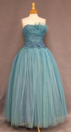 A fantastic vintage prom dress in turquoise blue tulle. Finely gathered bodice with asymmetrical fan bust. Terrific lace appliqued waist woven with pleated acetate bands. Large bow at rear waist. Dress has a layered, full skirt (shown here with a crinoline... not included). Rear metal zipper. Lined. Bodice is boned.