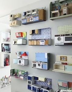 Collection of doll kitchens from the 1950s to 1970s, displayed on a wall as 3D art. Originally via shop.zoedelascases.com.