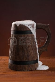 Caneca de cerveja de madeira com cerveja e espuma de p sobre uma mesa de madeira sobre fundo vermelh Banco de Imagens