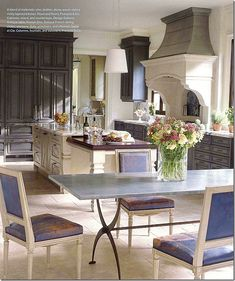 In Suzanne Kasler's client's house, the blue leather antique Louis XVI chairs are used in their kitchen.