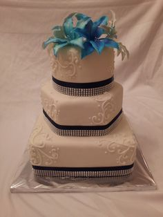 Sapphire Blue wedding cake with multi- color blue and silver lilies by @Heather Creswell Creswell Singleton at Party Delights