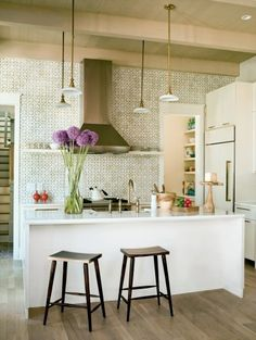 small and functional sleek modern kitchen….white cabinets, wood floor…love the tile on the wall!