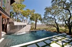 Kiawah Island, S.C.:  majestic great oaks surround a vanishing-edge Jacuzzi with a waterfall that flows into a vanishing-edge pool. There's a hot and cold shower at pool [more] level, plus a pool bathroom, a covered patio and a screened porch.