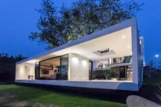 The sleek and simple volume connected with the main house acts as a den where you can relax, chat with friends or host casual parties. Ample use of white and sliding glass doors ensure that this structure looks bright and helps you to connect with nature easily. Houses by Yucatan Green Design