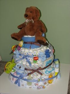 Cake made from disposable diapers and decorated with various baby items.