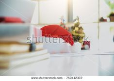 Christmas equipment with santa hat on office table in last working day. Young creative people are celebrating holiday in modern office. Merry Christmas and Happy New Year 2018