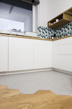 Białe szafki o gładkich frontach bez uchwytów wprowadzają nieco nowoczesnego charakteru do skandynawskiej kuchni....