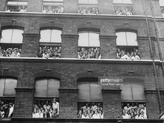 Female workers watching the coronation procession of King George V and Queen Mary from factory windows in London.