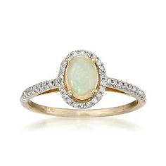 Our beautiful opal and diamond ring showcases an oval opal with great play of color on a band lit with diamonds. 14kt white gold ring. So lovely.