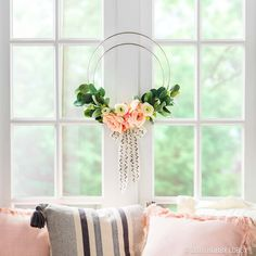 Simple yet stunning, this DIY hoop wreath really brings the chic. To DIY: 1) Wire 2 steel rings together at one point with floral wire. 2) Secure florals onto the hoops with floral wire. 3) Finish off with a trendy bow.