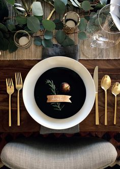 the holiday table, greenery, votive candles, gold flatware, black and white plate, gray linen napkins, name tags, place settings