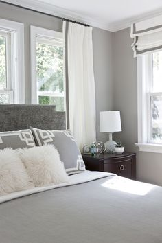 Gray bedroom features gray walls framing gray velvet headboard with silver nailhead trim accented with white and gray bedding and white and gray Greek key pillows situated in front of window dressed in white curtains with gray ribbon trim. I like the mix of curtains and shades that match.