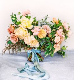 A blooming pastel hued bouquet with touches of peachy pink, golden yellow, soft orange and tied with a pale blue ribbon. Reminiscent of the ocean and the colors of the sunset.