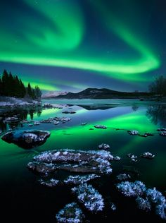 Norway. A wonderful display of northern lights dancing over a partially frozen river. by Arild Heitmann