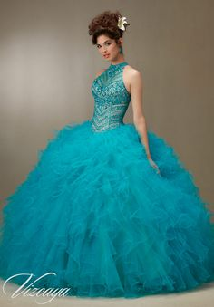 Blue Jeweled Beading on a Ruffled Tulle Princess Ball Gown Quinceanera Dress. High Neck by Vizcaya Designed by Madeline Gardner. Matching Stole included. Colors available: Scarlet/Nude, Capri/Nude and Champagne/Blush, White.