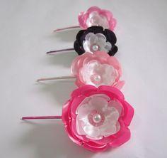 Kit com 4 grampos flores de cetim tons de rosa e roxo.