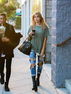 Hailey Baldwin wears a t-shirt, distressed jeans, a Givenchy duffle bag, and black Givenchy boots