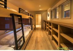Interior Design Ideas For Sleeping Six People In A Room // These built-in bunk beds in a home designed by Swaback Partners, line the entire side of the room, with storage opposite. The lower beds also have screens to separate them.
