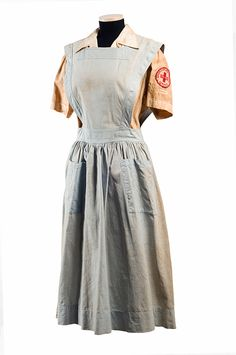 This was the standard nurse's aides corps uniform for the Red Cross – a blue cotton jumper apron that buttons down the back and has two large patch pockets on the skirt with a white regulation shirt underneath. The Red Cross Civilian Defense Nurse's Aid patch is sewn two inches below the shoulder seam of the left sleeve. c.1940s