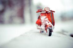 Zweirad-Pause: Eine rote Vespa-Miniatur mit  Schnee-Dekoration