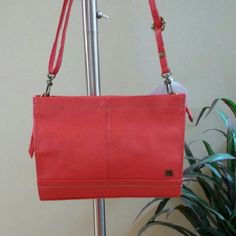 """Coral Color Leather Bag by The Sak Rich coral color, genuine leather purse with stitching detail. Very versatile purse can be used three ways - as a clutch or with the detachable straps as a shoulder purse or cross body.  Back pocket could be used for your cell phone. Top zipper closure. One inside zippered pocket. NWOT.  Approximate measurements:  10"""" long, 7"""" tall, 2-3/4"""" deep. Strap is approximately 23"""" when doubled. The Sak Bags"""