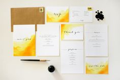 A water-coloured wedding stationery suite. Minimalistic flowing typography on a background of yellow watercolour.