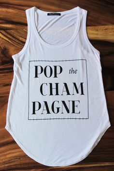 """This white semi-sheer muscle tank features """"Pop The Champagne"""" graphic on the front. Tank has a super lightweight, soft, stretchy, semi-loose fit. Style this popular top with some distressed jeans and"""