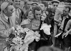 Il ciclista francese Roger Hassenforder dopo aver vinto la quinta tappa del Tour de France del 1955, insieme ai fan e alla cantante francese Annie Cordy (a sinsitra)