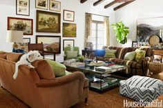 "Eric Stonestreet wanted his living room ""to be a place he can go with a Scotch and a cigar and enjoy a roaring fire,"" says designer Nathan Turner, who covered one of a pair of George Smith sofas in a corduroy and the other in Hopi First Phase Stripe, both from Ralph Lauren Home. Souk pouf by West Elm. Harbinger's Gould coffee table. Curtains in Samarkand by Peter Dunham Textiles."