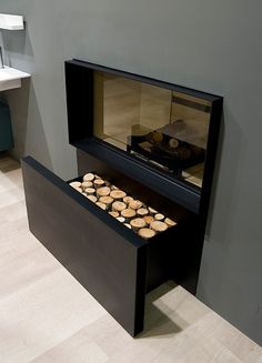 Skemabox is a gas log fireplace by Antonio Lupi. Equipped with a brazier and roll-away log compartment