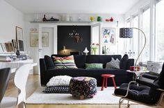 Sofá preto com almofadas em tamanhos e formas diferentes