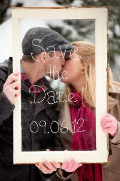 Save the date photo idea- couple holding up framed glass with wedding date written on it- couple is kissing behind the frame