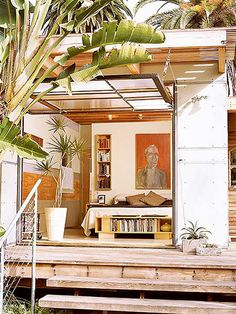 Open living room, garage door, plants, library, painting, wooden stairs