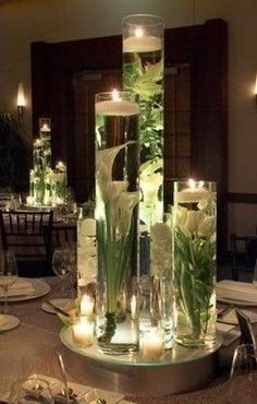 Glass vases & plants with floating & scattered candles make pretty centerpieces.