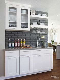 Close enough for easy access but still comfortably distant from the work zone, this wet bar features a rich contrast of white cabinetry, gray countertops, and a deep gray brick wall. Open shelves provide a place to hang wineglasses, stash napkins, and display vintage barware.