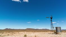 A static daytime timelapse of a typical arid Karoo farm landscape, a windmill blowing in the wind next to an old metal dam, scattered cumulous clouds forming against a bright blue sky. Windmill, Hd Video, Geology, Stock Footage, Wind Turbine, South Africa, African, Clouds, Bright